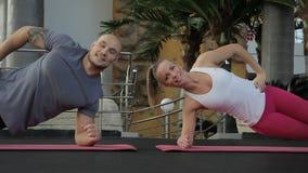 L'uomo e la donna allegri si esercitano sulle mani sulla stuoia in palestra archivi video