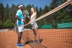 L'uomo e la donna allegri stanno giocando a tennis faccia a faccia immagini stock libere da diritti
