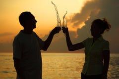 L'uomo e la donna clink i vetri. Spruzza di vino. Fotografia Stock Libera da Diritti