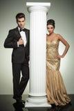 L'uomo e la donna convenzionali in vestiti di sera si avvicinano alla colonna Fotografia Stock
