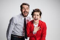 L'uomo e la donna di affari che ridono su un fondo grigio fotografia stock libera da diritti