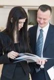 L'uomo e la donna di affari stanno considerando la rivista fotografie stock