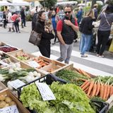 L'uomo e la donna esaminano le verdure sul mercato dell'aria aperta di briancon nell'Alta Provenza francese Fotografie Stock