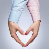 L'uomo e la donna fanno una forma di un cuore con le mani Fotografie Stock Libere da Diritti