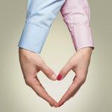 L'uomo e la donna fanno una forma di un cuore con le mani su backg giallo Fotografie Stock Libere da Diritti