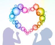 L'uomo e la donna gonfiano le bolle sotto forma di cuore Fotografia Stock Libera da Diritti