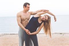 L'uomo e la donna incinta stanno facendo l'yoga sulla spiaggia Immagini Stock