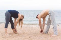 L'uomo e la donna incinta stanno facendo l'yoga sulla spiaggia Fotografie Stock Libere da Diritti