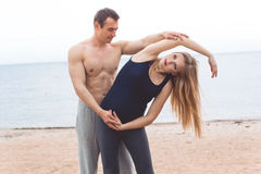 L'uomo e la donna incinta stanno facendo l'yoga sulla spiaggia Immagine Stock Libera da Diritti