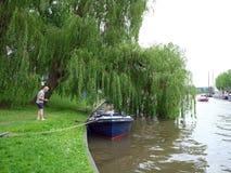 L'uomo e la donna parcheggiano la loro barca sotto l'albero di salice nel centro di vecchio Fotografia Stock
