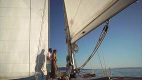 L'uomo e la donna quitely stanno guardando il tramonto a bordo dell'yacht archivi video