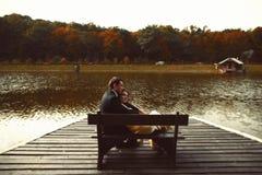 L'uomo e la donna riposano sul banco nel lago Fotografia Stock Libera da Diritti
