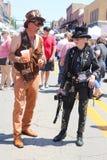 L'uomo e la donna si sono agghindati in costumi dello steampunk che stanno e che parlano nella via circondata dalla gente ad un f fotografia stock libera da diritti