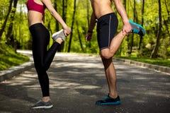 L'uomo e la donna sportivi stanno esercitando in natura Immagini Stock Libere da Diritti