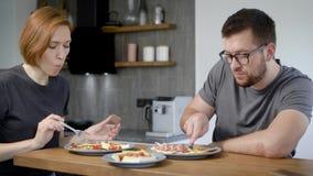 L'uomo e la donna stanno avendo prima colazione in cucina della loro casa nella mattina, prendente le uova rimescolate archivi video