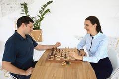 L'uomo e la donna stanno giocando gli scacchi Immagini Stock