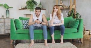 L'uomo e la donna stanno scegliendo il canale televisivo per guardare, uomo sta girando i programmi stock footage