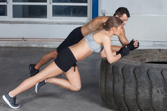 L'uomo e la donna su un addestramento di forma fisica del crossfit della gomma si scaldano Fotografie Stock