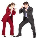 L'uomo e la donna in vestiti di affari stanno andando combattere Fotografie Stock Libere da Diritti