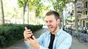 L'uomo eccitato usa un telefono e gli sguardi alla macchina fotografica archivi video
