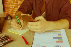 L'uomo ed il computer stanno utilizzando un calcolatore sulla tavola nell'ufficio Concetto di affari e di contabilità L'uomo si s Fotografia Stock Libera da Diritti