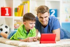 L'uomo ed il figlio scherzano il gioco con il computer della compressa Immagini Stock Libere da Diritti