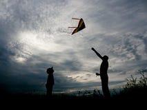 L'uomo ed il ragazzo lanciano un aquilone contro un bello tramonto dell'estate Immagine Stock