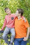 L'uomo ed il ragazzo stanno parlando lo sguardo con ogni altri Immagine Stock