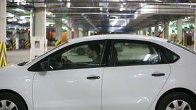 L'uomo entra nell'automobile indossare le cinture di sicurezza e tranquillamente va video d archivio