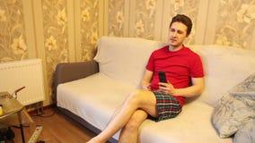 L'uomo entra nella stanza, si siede sul sofà stock footage
