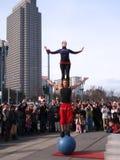 L'uomo equilibra sulla sfera blu mentre una signora si leva in piedi su lui Fotografie Stock