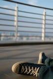 L'uomo era scarpa da tennis si siede sopra costruzione Immagine Stock