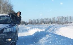 L'uomo esamina fuori la finestra di automobile la strada innevata in st della neve Immagini Stock
