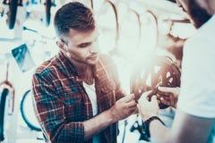 L'uomo esamina il casco per i giri della bici nel deposito di sport fotografia stock libera da diritti