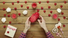 L'uomo esamina il cuore umano di plastica dalla tavola di legno, vista superiore stock footage