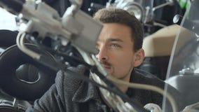 L'uomo esamina la ruota del motociclo che mostra il pollice su archivi video