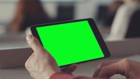 L'uomo esamina lo schermo della compressa con uno schermo verde azione Chiave di intensità sullo schermo della compressa nelle ma immagine stock