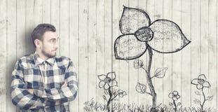 L'uomo esamina un fiore estratto Fotografie Stock