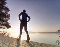 L'uomo esile alto sta correndo lungo il lago in parco nell'alba soleggiata fotografia stock libera da diritti