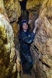 L'uomo esplora la caverna stretta fotografie stock