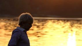 L'uomo europeo pratica l'yoga sulle radici dell'albero al tramonto stock footage