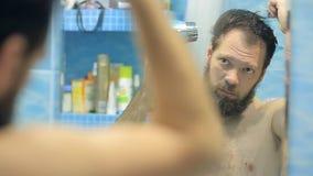 L'uomo europeo soffia i capelli asciutti e la barba nel bagno davanti allo specchio video d archivio