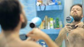 L'uomo europeo soffia i capelli asciutti e la barba nel bagno davanti allo specchio stock footage