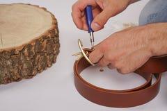 L'uomo fa dalla cinghia di cuoio delle mani con il fermaglio Hobby fatto a mano giovane che riposa dalla fabbricazione le sue cin immagini stock