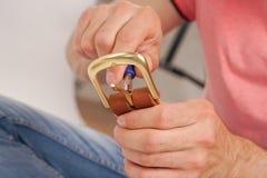 L'uomo fa dalla cinghia di cuoio delle mani con il fermaglio Hobby fatto a mano giovane che riposa dalla fabbricazione le sue cin immagine stock