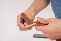 L'uomo fa dalla cinghia di cuoio delle mani con il fermaglio Hobby fatto a mano giovane che riposa dalla fabbricazione le sue cin fotografie stock libere da diritti