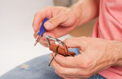 L'uomo fa dalla cinghia di cuoio delle mani con il fermaglio Hobby fatto a mano giovane che riposa dalla fabbricazione le sue cin fotografie stock