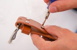 L'uomo fa dalla cinghia di cuoio delle mani con il fermaglio Hobby fatto a mano giovane che riposa dalla fabbricazione le sue cin fotografia stock libera da diritti