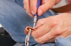 L'uomo fa dalla cinghia di cuoio delle mani con il fermaglio Hobby fatto a mano giovane che riposa dalla fabbricazione le sue cin immagini stock libere da diritti