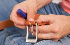L'uomo fa dalla cinghia di cuoio delle mani con il fermaglio Hobby fatto a mano giovane che riposa dalla fabbricazione le sue cin immagine stock libera da diritti
